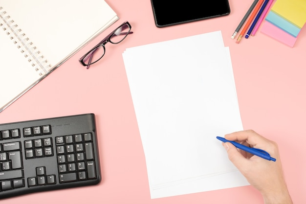 White clean sheets for records, hand holds pen, office glasses. flat lay. office content. pink table