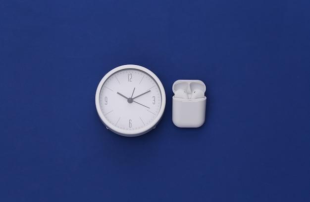 고전적인 파란색 배경의 충전 케이스에 있는 흰색 시계와 무선 이어폰.