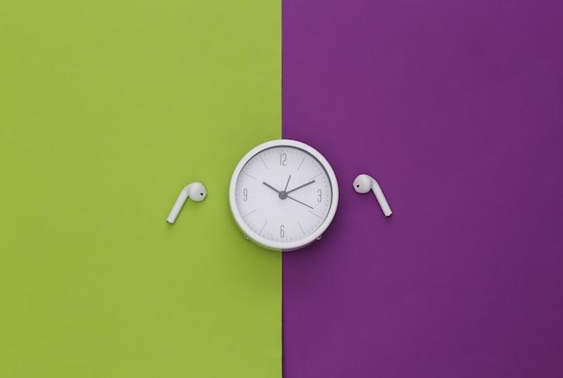 보라색-녹색 배경에 흰색 시계와 무선 이어폰.