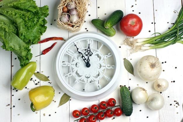 샐러드를 만들기 위해 다른 야채 중간에 흰색 시계