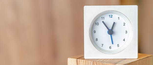 White clock on a wooden surface. blurred wooden wall. copy space