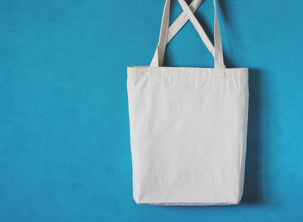 White cloth bag with straps hangs