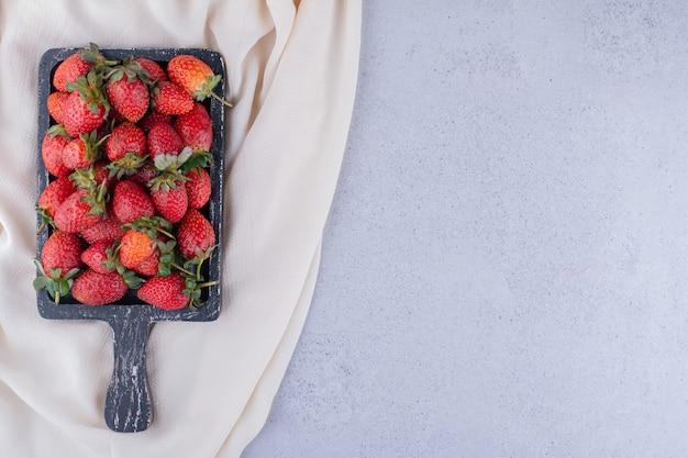 대리석 배경에 쌓인 딸기 쟁반 아래에 있는 흰색 천. 고품질 사진