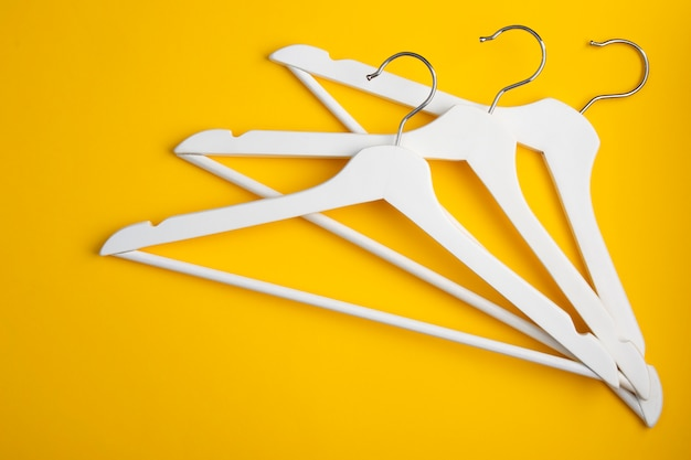 White clothes hangers on yellow. store concept