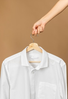 Vestiti bianchi sulla gruccia con l'etichetta dello spazio della copia di informazioni