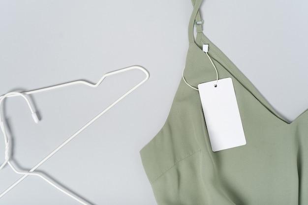 흰색 의류 태그, 빈 모형 템플릿에 레이블을 지정합니다. 프리미엄 코튼 카키 그린 블라우스에 옷걸이에