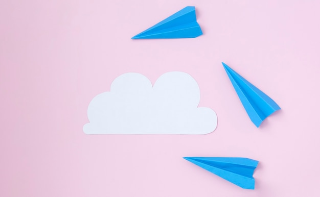White cloud of paper and paper planes on a pink background