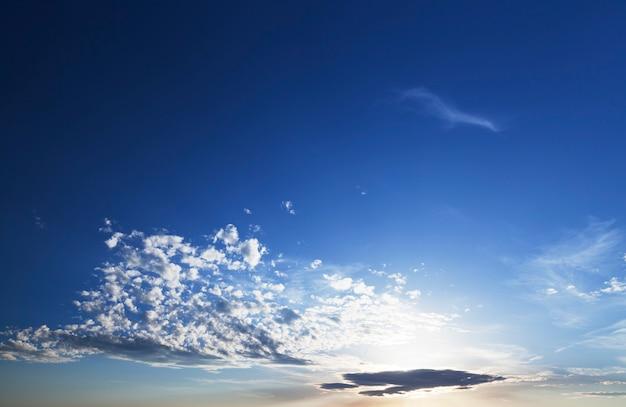 일출 동안 흰 구름과 푸른 하늘, 태양의 구름을 통해 밝게 빛나는 따뜻한 색, 풍경