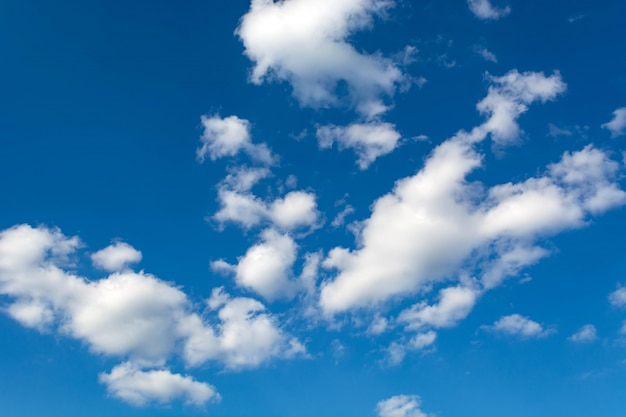 White clouds on a clear blue sky background