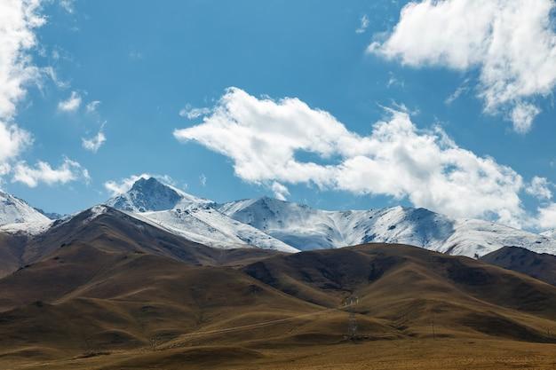白い雲が山の上に浮かんでいます。キルギスタンの山の風景