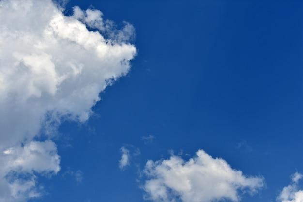 白い雲が青い空を横切って飛ぶ