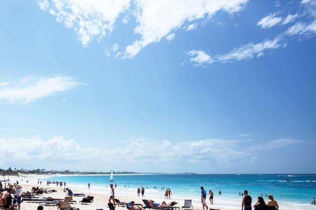 Белые облака висят над солнечным пляжем, где отдыхают люди