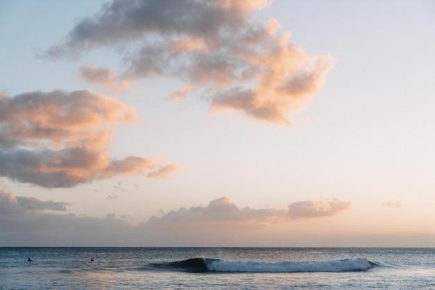 海の夕日の光と空に白い雲