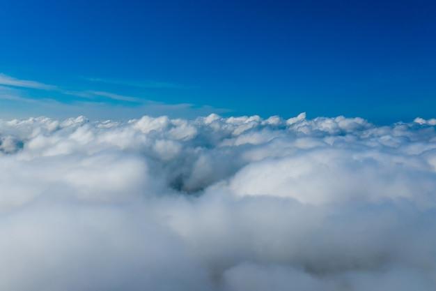 白い雲。飛行機の窓からの眺め。下の雲と上の青い空。