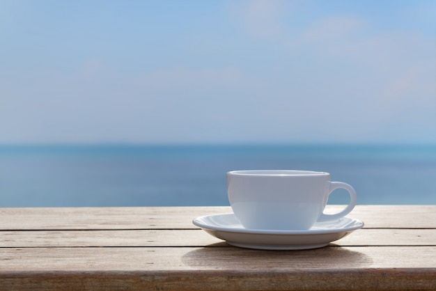 White coffe cup on wood table top with blurred sea sky background