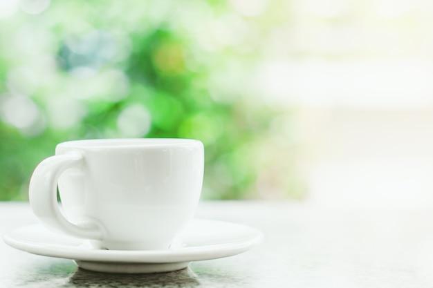 ドリンクと飲み物のコンセプトのためのぼんやりとした自然の緑の背景に対する白いコーヒーカップ