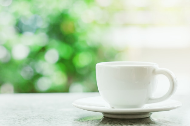 White coffee cup against blurred natural green background