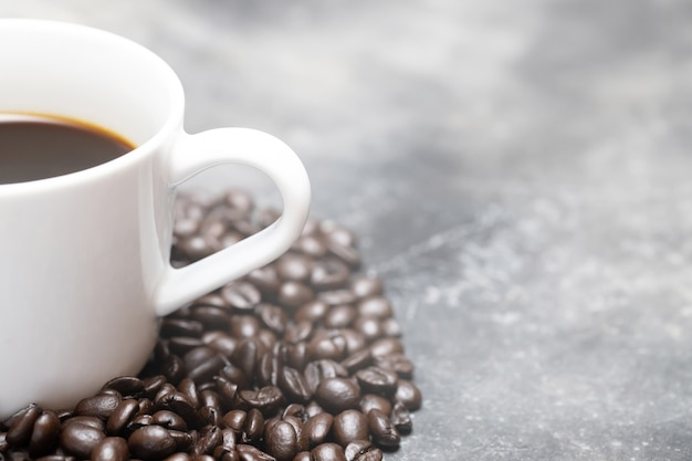 Белая кофейная чашка и кофейные зерна темные на столе