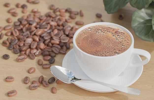 화이트 커피 컵과 식물을 가진 나무 테이블에 커피 콩