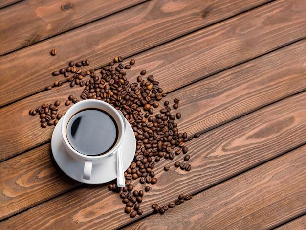 Белая кофейная чашка, фасоль и ложка на деревянных на столе.