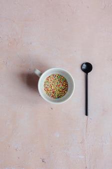 Белая кофейная чашка, наполненная конфетами и черной ложкой на розовом фоне в возрасте.