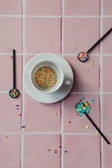 Белая кофейная чашка, наполненная конфетами, и черная ложка на фоне счетчика розовой плитки