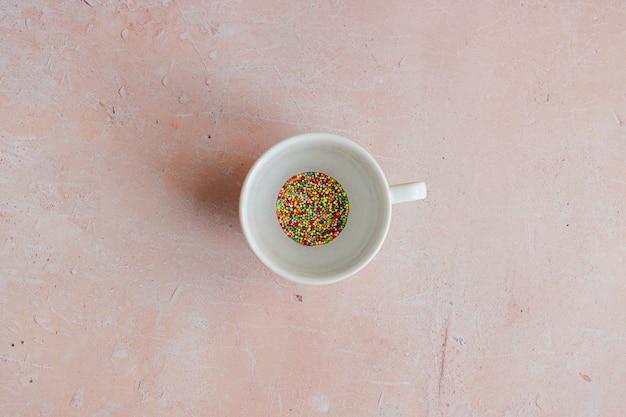 Белая кофейная чашка, наполненная конфетами, разбрызгивается на розовом фоне бетона.