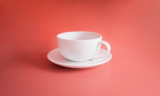 オレンジ色のパステルカラーの背景またはオレンジ色の背景に分離された白いコーヒーカップ
