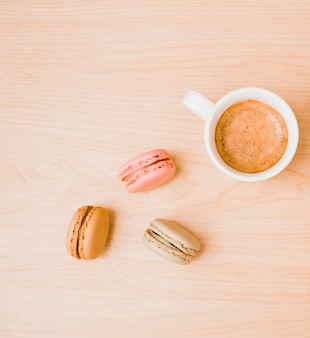 White coffee cup and macaroons on wooden textured backdrop