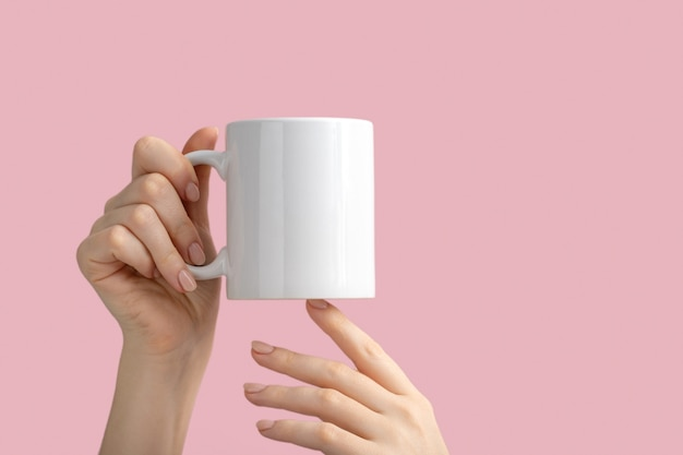 White coffee cup or mug in female hands on pink