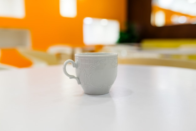 カフェの白いテーブルの上の白いコーヒーカップ