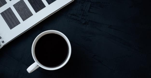 黒いテーブルの上の白いコーヒーカップ