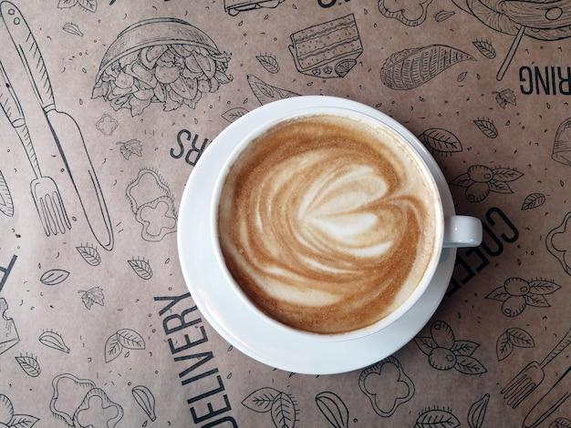 Белая кофейная чашка на пергаментной бумаге с узором