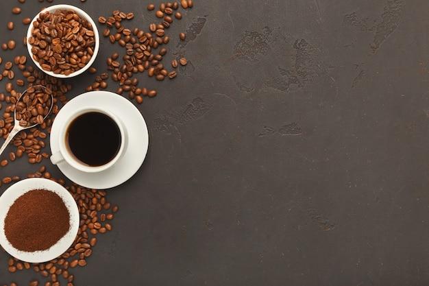 Белая кофейная чашка на блюдце и разбросанные жареные бобы на сером текстурированном фоне, вид сверху. минималистичный дизайн для рекламы кафе, копировальное пространство