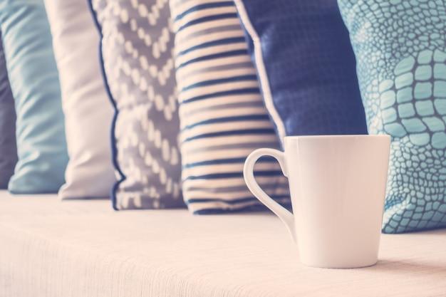Белая кофейная чашка на диване с подушкой в интерьере гостиной