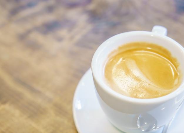 カフェでテーブルの上に白いコーヒーカップ