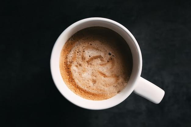 Белая кофейная чашка на темно-сером