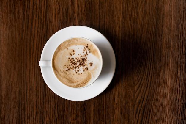 Белая кофейная чашка на деревянном столе