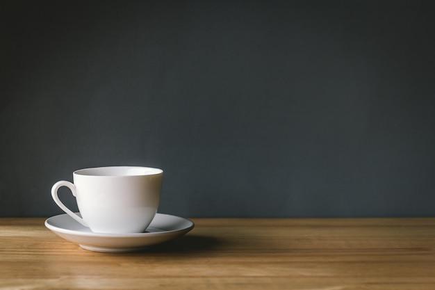 灰色の背景を持つ木製の机の上の白いコーヒーカップ