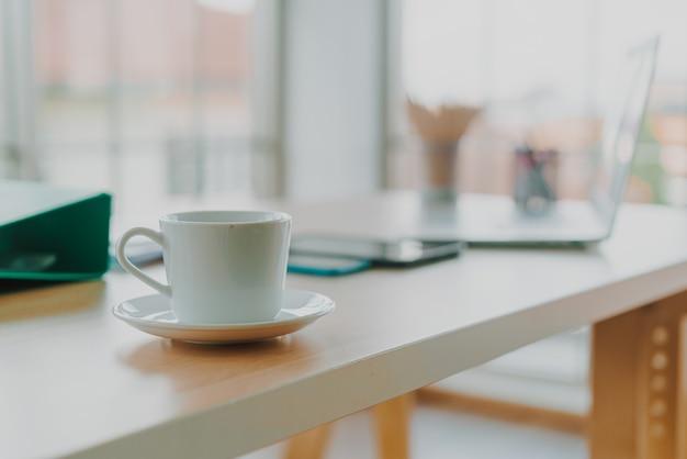 Белая кофейная чашка на рабочем столе - эффект винтажного фильтра