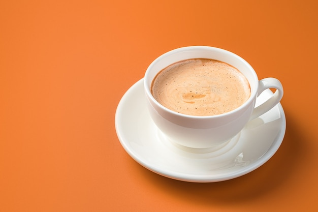 White coffee cup on orange wall with copy space. side view.