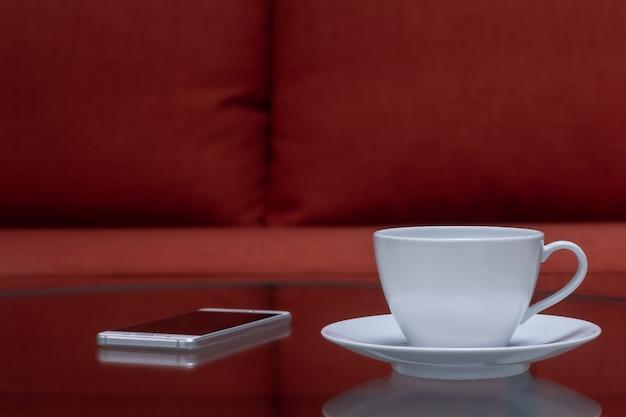 ぼやけたスマートフォンと赤い布のソファの近くのミラーテーブルに置いた白いコーヒーカップ