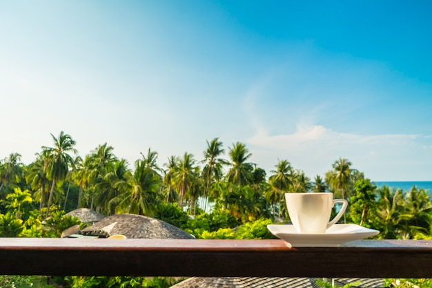 White coffee cup with beautiful paradise island sea and beach