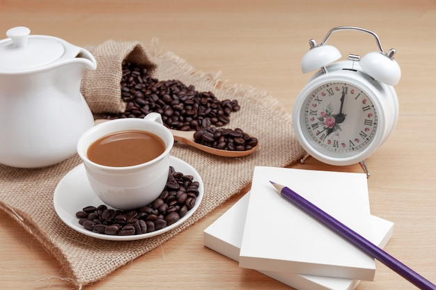 White coffee cup with coffee beans and alarm clock on wooden background