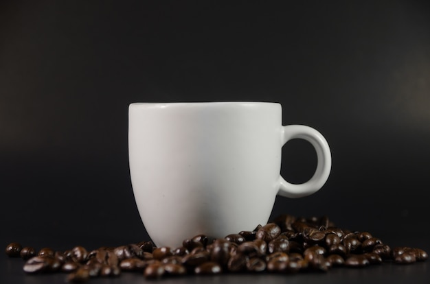 White coffee cup with coffee beans on black background