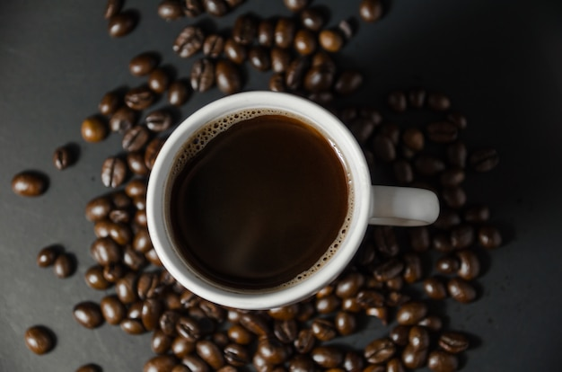 White coffee cup with coffee beans on top view