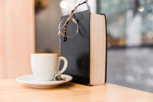 White coffee cup with eyeglasses and book on wooden table