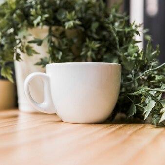 Белая чашка кофе с горшечным растением на деревянном столе