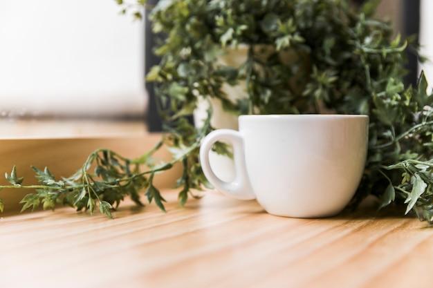 Белая чашка кофе с горшечным растением на деревянной столешнице
