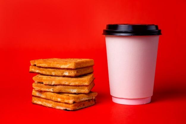 Белая кофейная чашка с вафлями на красном.